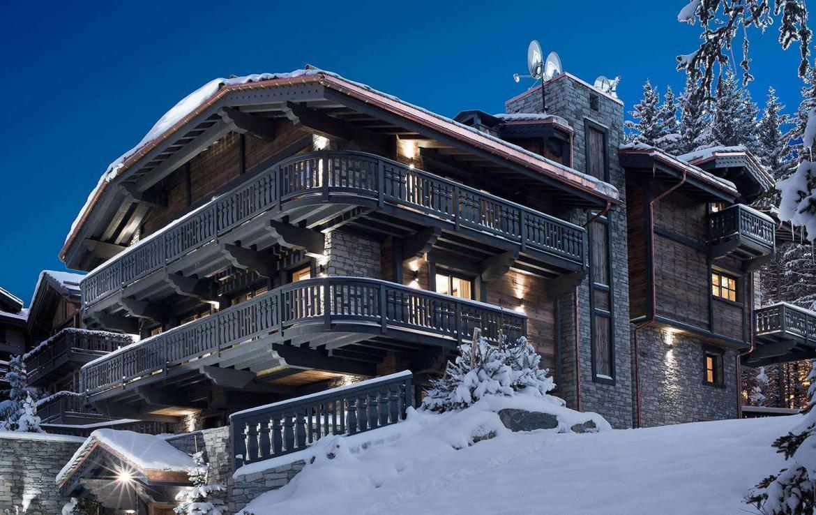 kings-avenue-luxury-chalet-courchevel-001-side-view-exterior-snow-with-blue-sky