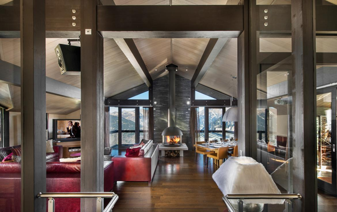 kings-avenue-luxury-chalet-courchevel-003-front-view-living-area-with-tv-dining-area-open-fireplace
