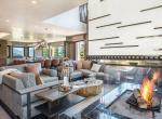 kings-avenue-luxury-chalet-courchevel-008-side-view-sitting-are-with-open-fireplace