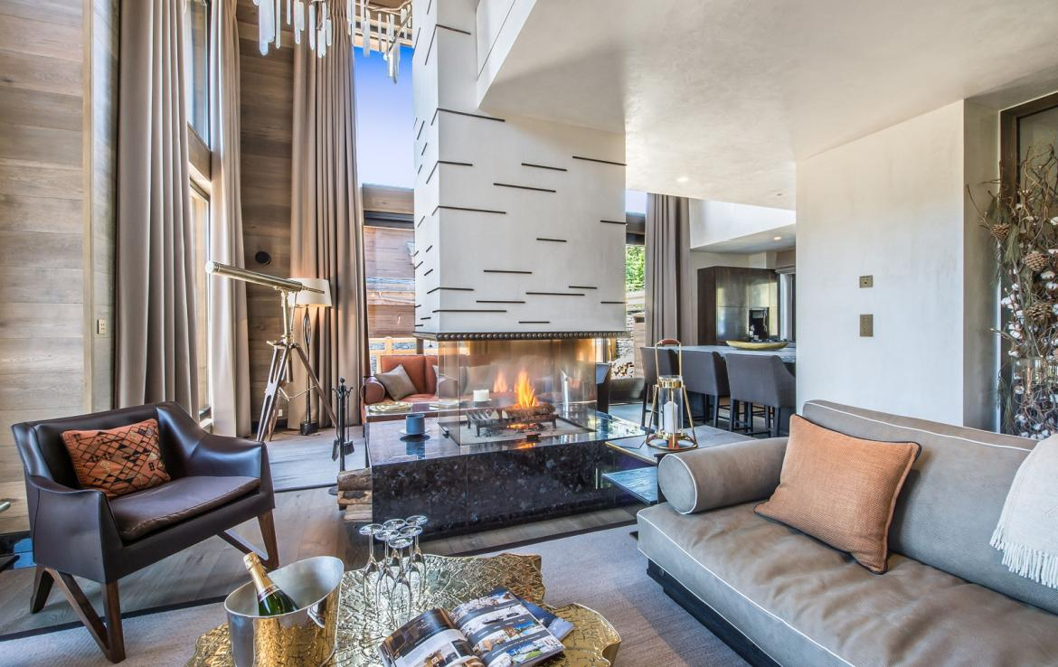 kings-avenue-luxury-chalet-courchevel-008-sitting-area-with-open-fireplace