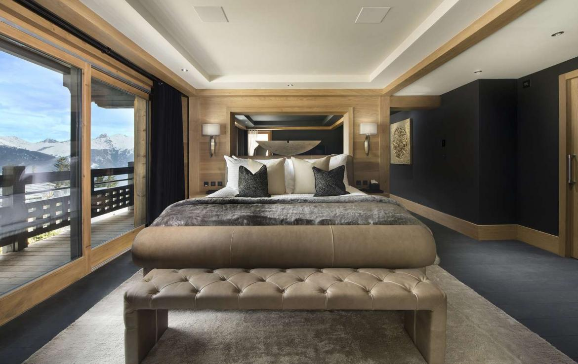 kings-avenue-luxury-chalet-courchevel-009-master-bedroom-with-balcony-and-mountain-views