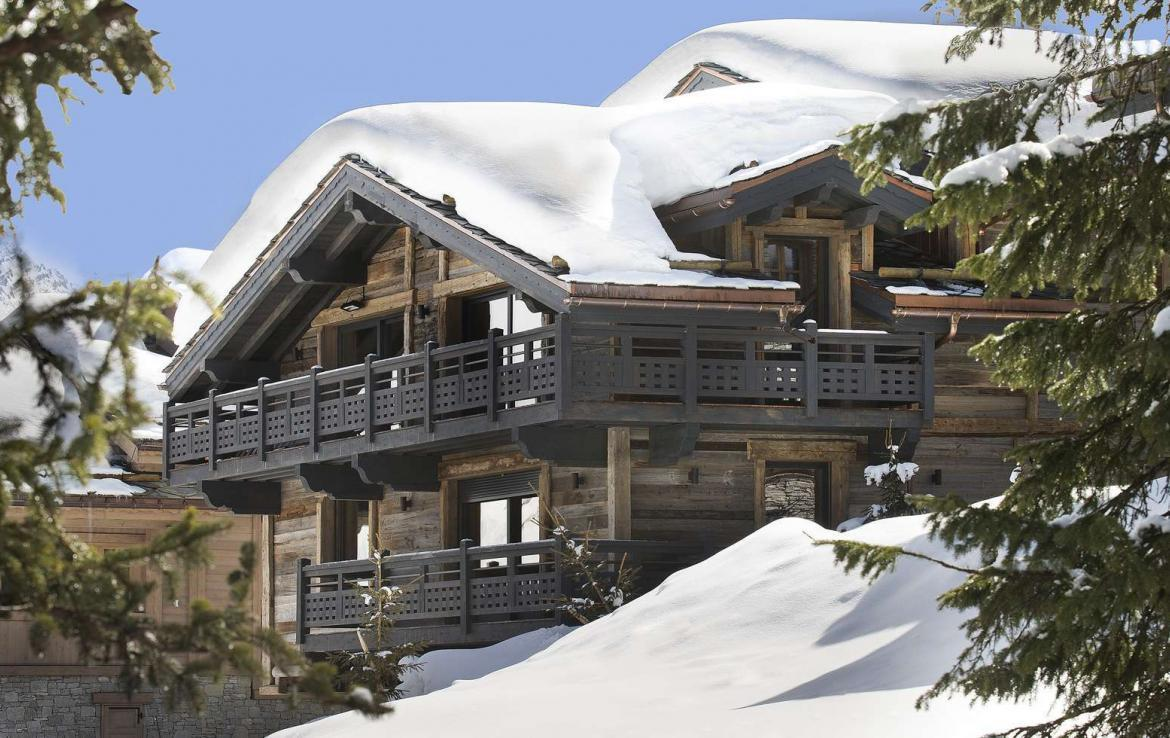 kings-avenue-luxury-chalet-courchevel-009-side-view-exterior-blue-sky-snow
