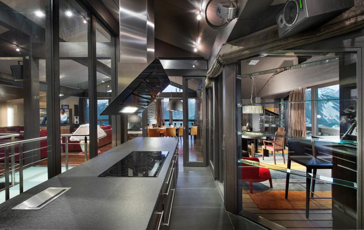 kings-avenue-luxury-chalet-courchevel-003-kitchen-background-living-area-and-dining-table-with-views