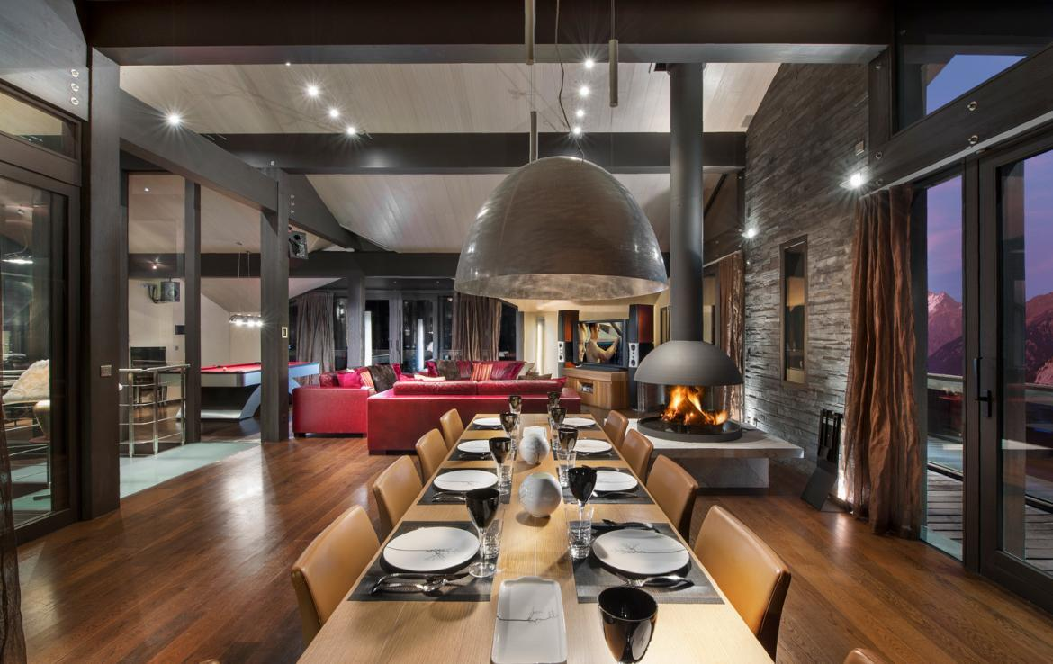 kings-avenue-luxury-chalet-courchevel-003-living-area-with-dining-table-and-open-fireplace