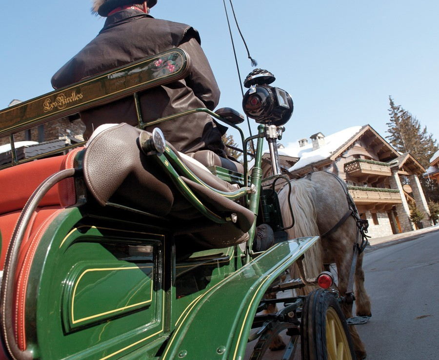 kings-avenue-luxury-chalet-courchevel-005-transport-with-horse-and-carriage-in-snow-with-blue-sky