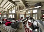 kings-avenue-luxury-chalet-courchevel-007-side-view-double-height-sitting-room-big-windows-with-mountain-views