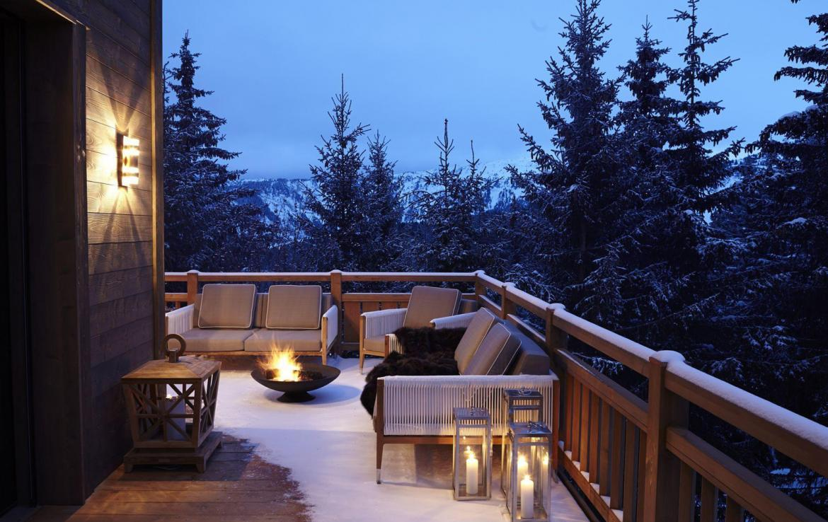 kings-avenue-luxury-chalet-courchevel-008-balcony-with-fireplace-and-mountain-views
