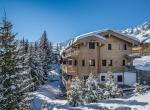 kings-avenue-luxury-chalet-courchevel-008-exterior-view-with-snow-mountains-blue-sky-and-pine-trees